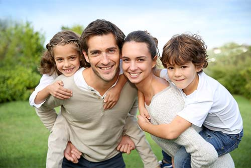 family of smiling people standing in a grassy field